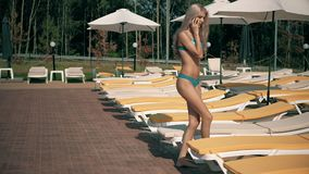 A BEAUTIFUL WOMAN RELAXS A SWIMMING POOL WITH BLUE WATER stock footage