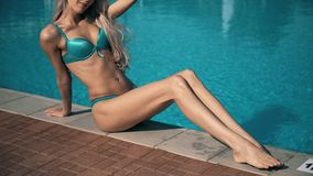 A BEAUTIFUL WOMAN RELAXS A SWIMMING POOL WITH BLUE WATER stock video