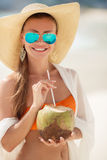 Beautiful woman removes thirst with coconut milk. Stock Photo