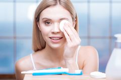 Beautiful woman removing eye makeup with cotton pad. After long day. Pleasant young woman in a white tank top standing in the bathroom and removing the make up Stock Photos