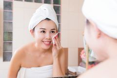 Beautiful woman removing makeup from her face in bathroom. Stock Images