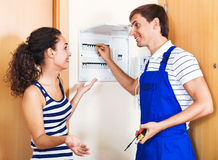 Beautiful woman and repairman near electric mete Royalty Free Stock Images