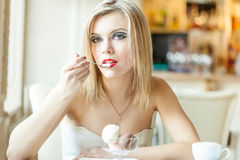 A woman in the restaurant is eating ice cream Royalty Free Stock Photos