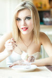 A woman in the restaurant is eating ice cream Royalty Free Stock Photo