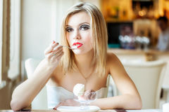 A woman in the restaurant is eating ice cream Stock Image
