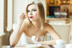 A woman in the restaurant is eating ice cream Stock Images