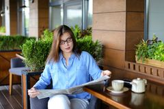 Pretty girl sitting at restaurant arm chair and reading newspape. Beautiful woman resting and reading newspaper articles at restaurant  . Charming female person Royalty Free Stock Images