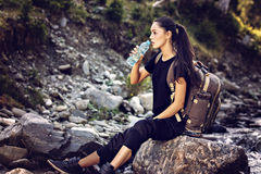 Beautiful woman resting on a rock in the river and drinking wate Stock Images