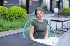 Beautiful woman resting at street cafe and sitting near green plant. Beautiful woman resting at street cafe and sitting in chair near green plant. Concept of Royalty Free Stock Photography