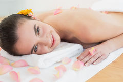 Beautiful woman resting on towel with petals at beauty spa Royalty Free Stock Photos
