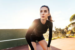 Beautiful woman resting after workout on tennis court. Portrait of beautiful young woman resting after workout on a sunny day. Sportswoman taking break after Stock Images