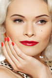 Beautiful woman with retro make-up & nail polish. 50s american retro blond model with vintage classic make-up. Red lips makeup, playful eyes with long lashes Stock Photos