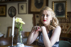 Beautiful  woman in retro style portrait sitting at a table in a cafe. Royalty Free Stock Photography