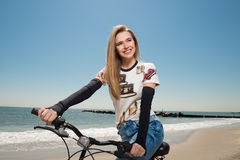 Beautiful woman ride on the beach on her bicycle at summer time Royalty Free Stock Photography
