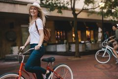 Beautiful woman riding bicycle in the city. Beautiful caucasian female riding bicycle in the city. Woman cycling and having fun on city street stock photos