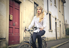Beautiful woman riding the bike Stock Photos