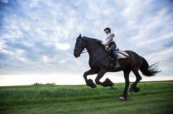 Beautiful woman riding a black friesian horse. stock photography