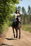 Beautiful woman riding gray horse in the forest Royalty Free Stock Photo