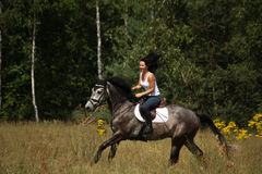 Beautiful woman riding gray horse in the forest. Beautiful woman riding gray horse near the forest Stock Photo