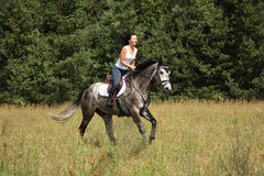 Beautiful woman riding gray horse in the forest Royalty Free Stock Images