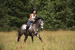 Beautiful woman riding gray horse in the forest Stock Photography