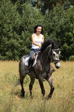 Beautiful woman riding gray horse in the forest. Beautiful woman riding gray horse near the forest Royalty Free Stock Photos