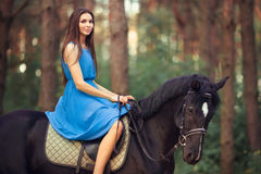 Beautiful woman riding horse in forest Stock Photo