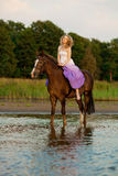 Beautiful woman riding a horse at sunset on the beach. Young bea Royalty Free Stock Image