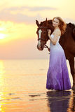 Beautiful woman riding a horse at sunset on the beach. Young gir Stock Image