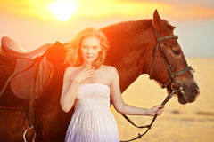 Beautiful woman riding a horse at sunset on the beach. Young gir Royalty Free Stock Images
