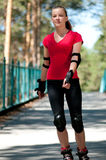 Beautiful woman rink on rollerskate in park Royalty Free Stock Photos