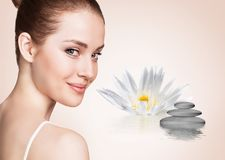 Beautiful woman in ripple water with lotus flower. Spa concept. Over beige background royalty free stock image