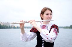 Beautiful woman on the river playing flute celtic medieval music Stock Photo