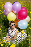 Beautiful woman with a rockabilly style dress sitting on a flowe Royalty Free Stock Images