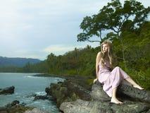Beautiful woman on a rocky seashore Royalty Free Stock Image