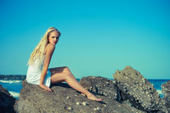 Beautiful woman on a rocky seashore. Photo of beautiful woman in wet clothes on a rocky seashore Royalty Free Stock Photography