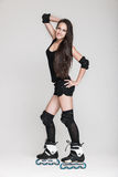 Beautiful woman in roller skates. Very attractive brunette woman with long hair in sexy outfit posing in studio wearing inline rollerskates, isolated on white Royalty Free Stock Images