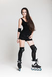 Beautiful woman in roller skates. Very attractive brunette woman with long hair in sexy outfit posing in studio wearing inline rollerskates, isolated on white Royalty Free Stock Photography