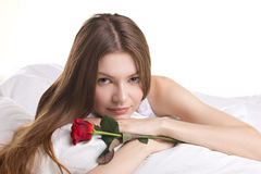 Beautiful  woman with rose in a bed Stock Image