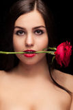 Beautiful woman with rose in hand on black Stock Image