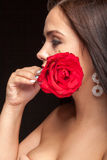 Beautiful woman with rose in hand on black Royalty Free Stock Photo