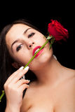 Beautiful woman with rose in hand on black Royalty Free Stock Images