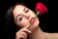 Beautiful woman with rose in hand on black Stock Photography