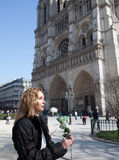Beautiful woman with a rose before Notre Dame de Paris Stock Image