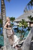 Beautiful woman with a rose at a palm tree. Bora-bora, Tahiti Royalty Free Stock Images