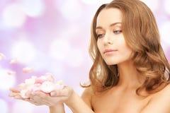 Beautiful woman with rose petals stock photography