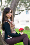 Beautiful woman with rose. Young beautiful woman with rose under the tree Royalty Free Stock Photo