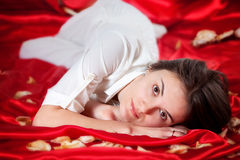 Beautiful woman with roses leaves, lying on red satin, represent. Young beautiful woman with roses leaves, lying on red satin, representing beauty concept royalty free stock photography