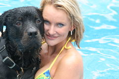 Beautiful woman & rottweiler. Model swimming with her rottweiler Stock Photos