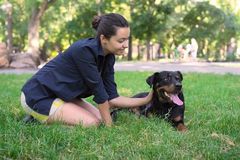 Beautiful woman and rottweiler in park Royalty Free Stock Photo